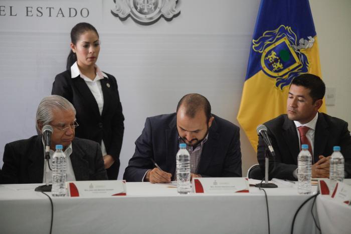Fotografía del Secretario Ricardo Villanueva sentado firmando un documento