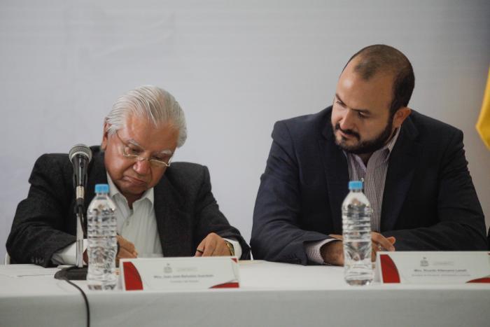 Fotografía del contralor José Luis Bueñuelos sentado firmando un documento